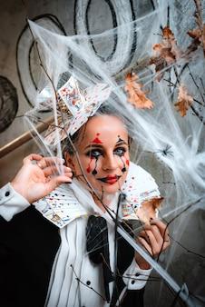 트릭 또는 치료. 할로윈 밤 파티를 방문하는 동안 거미줄을 통해 카메라를 보고 있는 카드 칼라와 함께 하트 여왕 의상을 입고 으스스한 화장을 한 젊은 여성의 초상화