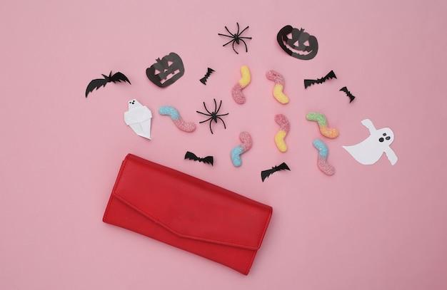 트릭 또는 치료. 수제 할로윈 종이 장식이 있는 지갑, 분홍색 파스텔 배경의 거미 벌레. 할로윈 배경입니다. 평면도. 플랫 레이