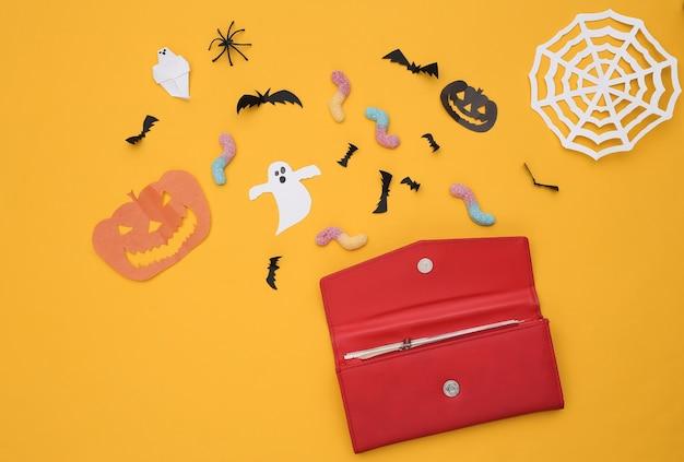 트릭 또는 치료. 수제 할로윈 종이 장식이 있는 지갑, 노란색 배경에 거미 벌레. 할로윈 배경입니다. 평면도. 플랫 레이