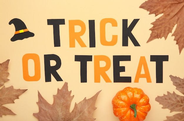 Trick or treat background with autumn leaves on beige. halloween concept