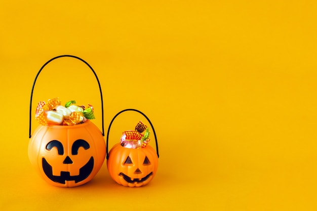 Trick or treat for halloween. pumpkin bucket with sweets and spiders on orange
