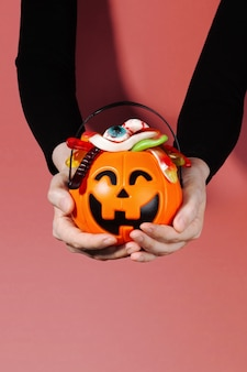 Trick or treat. pumpkin jack filled with various creepy sweets stands on stones and moss. woman hand holds basket