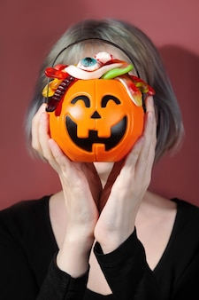 Trick or treat. pumpkin jack filled with various creepy sweets. woman holds basket. trend without face