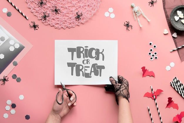 Trick or treat text on pink paper. flat lay with hands with scissors and halloween decor.