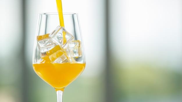 흐릿한 배경에 얼음 조각이 있는 유리에 쏟아지는 신선한 오렌지 주스의 물방울