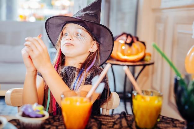 トリックとお菓子。グミのお菓子を食べながらトリックをするハロウィーンのスーツを着ている美しい青い目の女の子