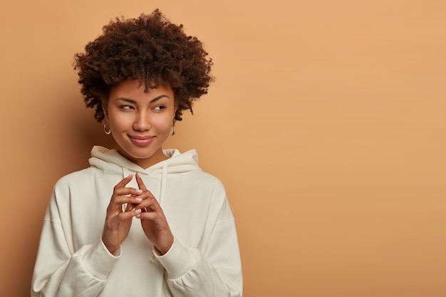 Tricky black woman has great evil plan, keeps hands together and looks with intention to do something, plans to do interesting thing