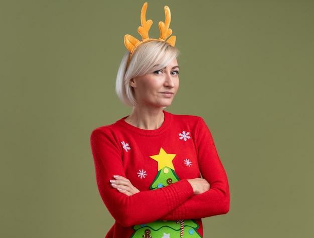 Хитрая блондинка средних лет в рождественской повязке на голову из оленьих рогов и рождественском свитере стоит в закрытой позе, глядя в камеру, изолированную на оливково-зеленом фоне с копией пространства