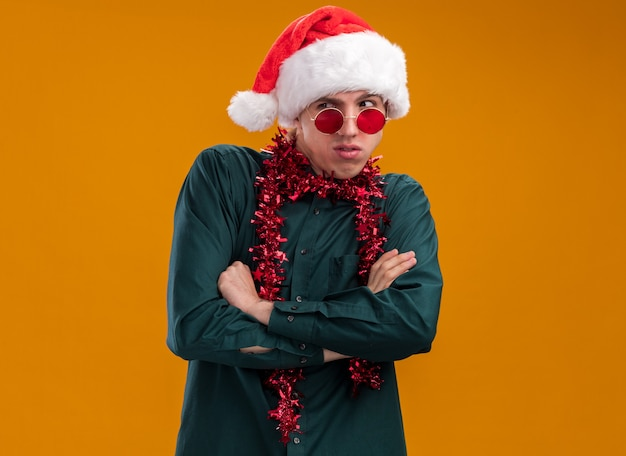 Tricky young blonde man wearing santa hat and glasses with tinsel garland around neck standing with closed posture looking at side isolated on orange background with copy space