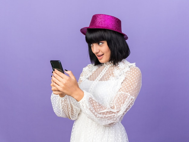 복사 공간이 있는 보라색 벽에 격리된 쪽을 바라보는 휴대전화를 들고 프로필 보기에 서 있는 파티 모자를 쓴 까다로운 젊은 파티 소녀