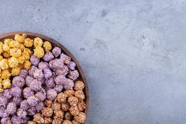 Трехцветная композиция из засахаренного попкорна на подносе на мраморной поверхности