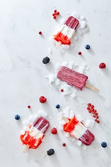 Tricolor strawberry and raspberry ice cream popsicles over ice with berries on marble background, top view and copy space