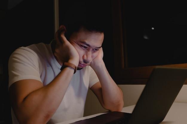 眠そうなアジア人男性は、夜遅くまでノートパソコンを持って仕事をしています。