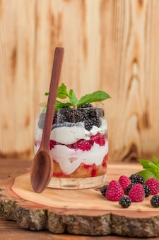 Trifle close up photography with fresh multi layered dessert with dairy raspberries and blackberries