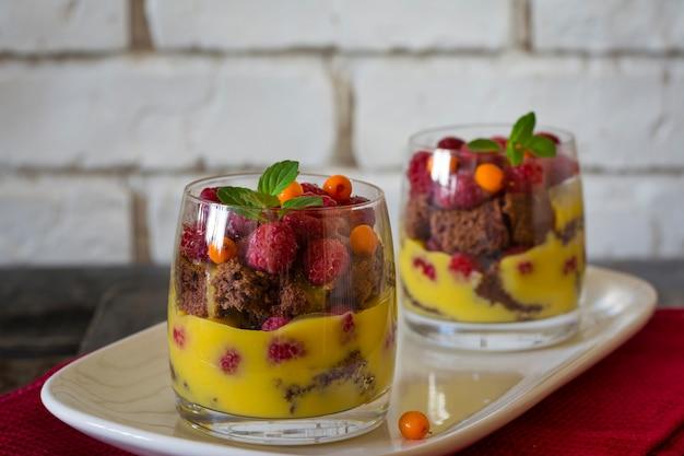 Trifle. dessert in glass. mousse in glass. orange curd. raspberry. mini cake. citrus dessert