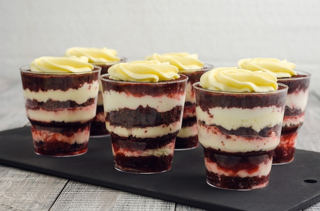 Trifle red velvet with cream on a black kitchen board.