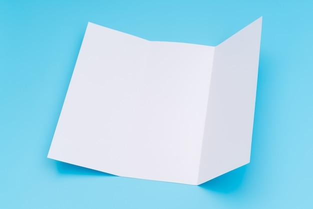 파란색 배경에 trifold 흰색 템플릿 종이입니다.