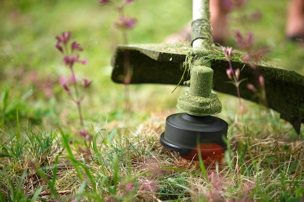 Тример косит траву крупным планом.