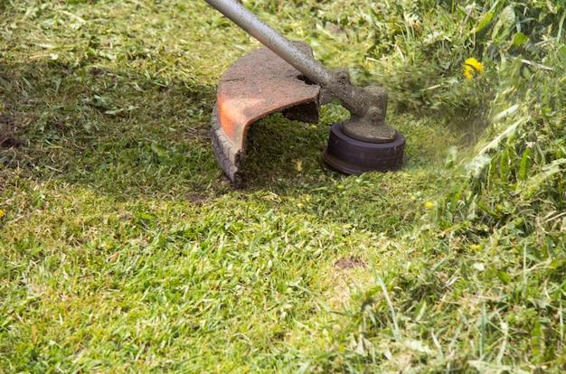 잔디를 깎는 트리머 또는 가솔린 침. 측면에서 봅니다.