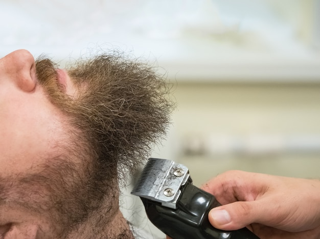 Стрижка бороды машинкой в парикмахерской. закройте вверх.