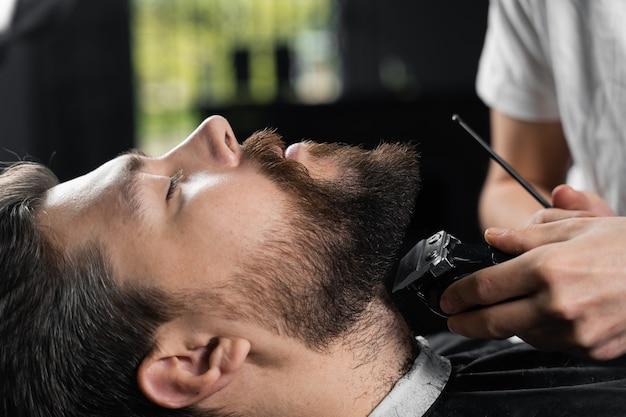 髭剃り機で髭を整えます。理髪店やメンズビューティーサロンの広告。