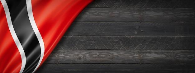 검은 나무 벽에 트리니다드 토바고 플래그입니다. 수평 파노라마 배너.