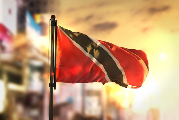 Trinidad and tobago flag against city blurred background at sunrise backlight
