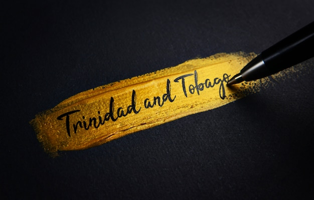 Trinidad and tobago handwriting text on golden paint brush stroke