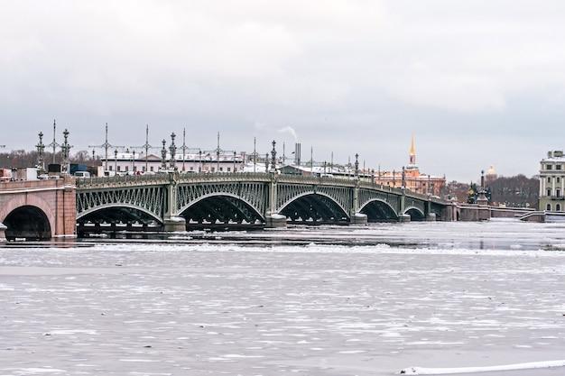 Троицкий мост в санкт-петербурге через замерзшую зимой неву.