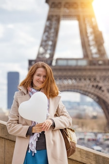 Trip across europe. girl with a balloon in the shape of a hearton the background of the eiffel tower in paris. france