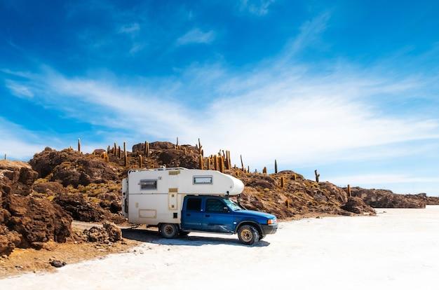 Trip car on the background of rocky sunshine cactus island salar de uyuni