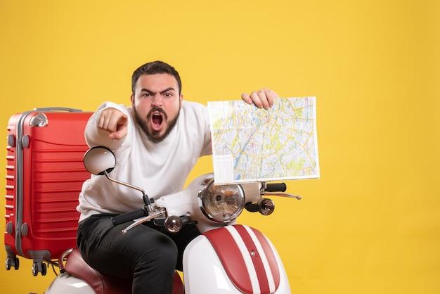 Concetto di viaggio con un ragazzo arrabbiato seduto su una motocicletta con la valigia sopra tenendo la mappa rivolta in avanti sul giallo