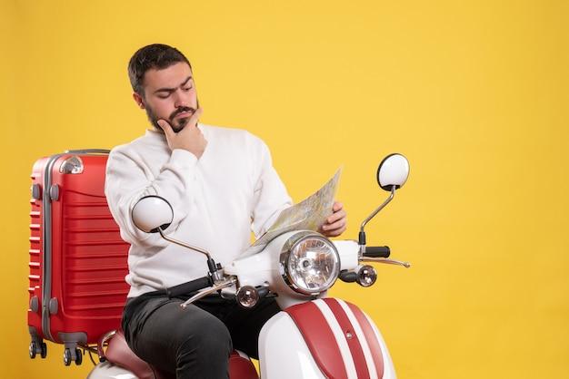 Concetto di viaggio con uomo impegnato seduto sulla moto con la valigia su di essa su giallo