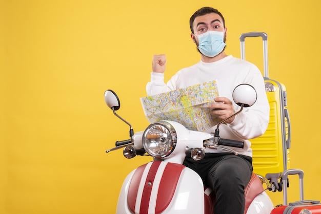 Концепция поездки с уверенным в себе парнем в медицинской маске, сидящим на мотоцикле с желтым чемоданом и держащим карту на желтом