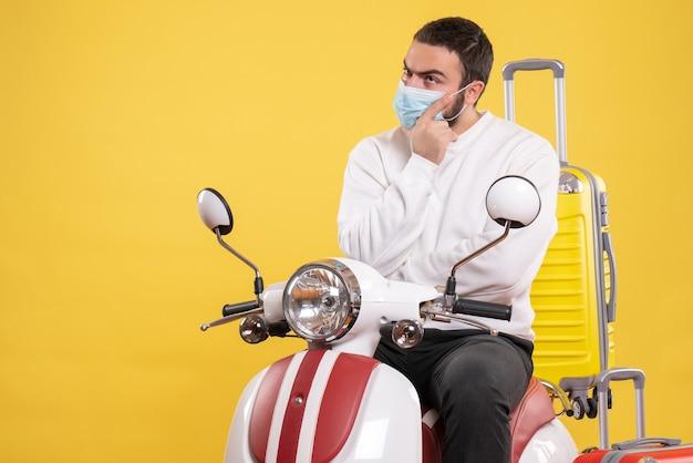 Concetto di viaggio con ragazzo confuso in maschera medica seduto su moto con valigia gialla su di esso su giallo