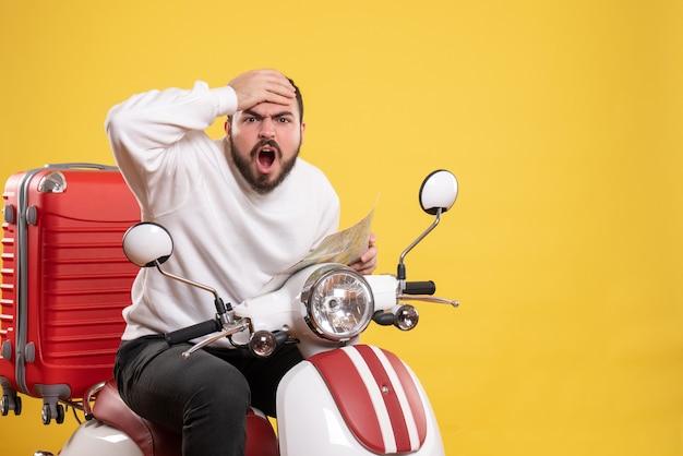 Концепция поездки с растерянным парнем, сидящим на мотоцикле с чемоданом на нем, держа карту на желтом