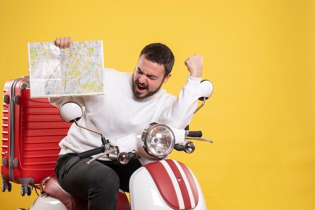 Концепция поездки со счастливым парнем, сидящим на мотоцикле с чемоданом на нем, показывая карту на желтом