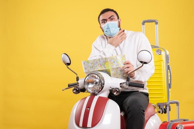 Концепция поездки с нервным парнем в медицинской маске, сидящим на мотоцикле с желтым чемоданом на нем и держащим карту, задыхаясь на желтом