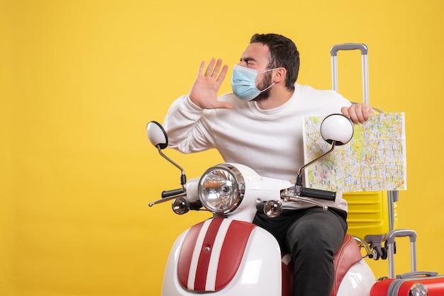 Концепция поездки с нервным парнем в медицинской маске, сидящим на мотоцикле с желтым чемоданом и показывающим карту на желтом