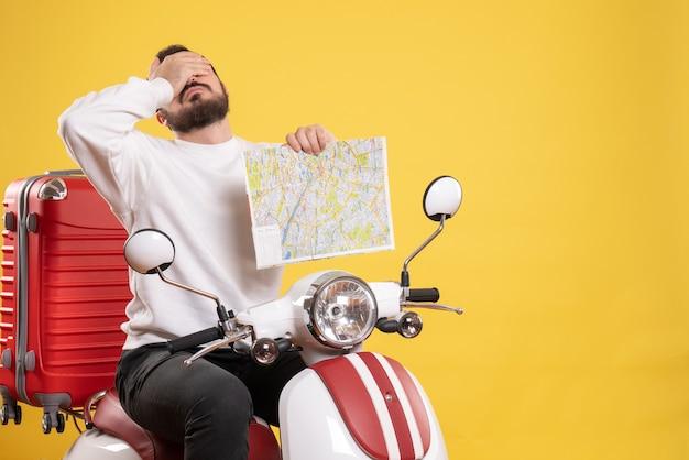 Concetto di viaggio con un ragazzo stanco seduto su una moto con la valigia su giallo