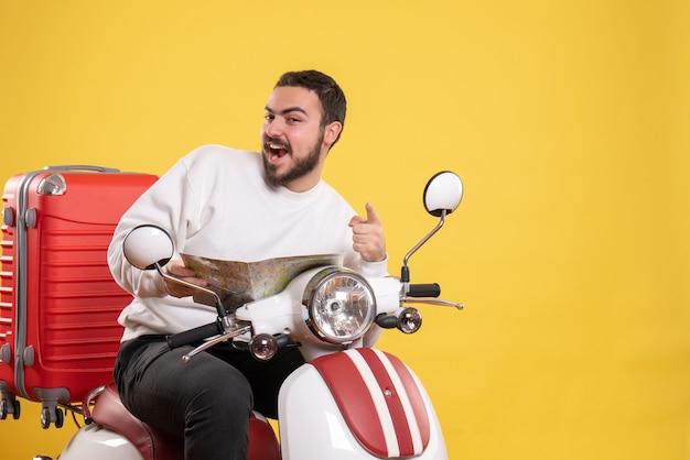 黄色の前方を指す地図を持ってスーツケースを持ってオートバイに座っている笑顔の男との旅行のコンセプト