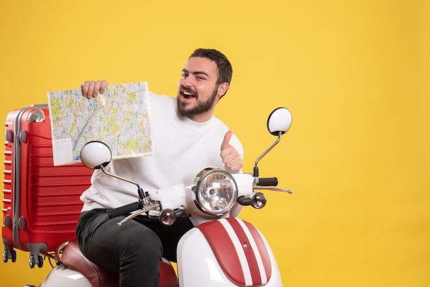 スーツケースを載せたバイクに座っている笑顔の男と、黄色でokのジェスチャーをする地図を示す旅行のコンセプト