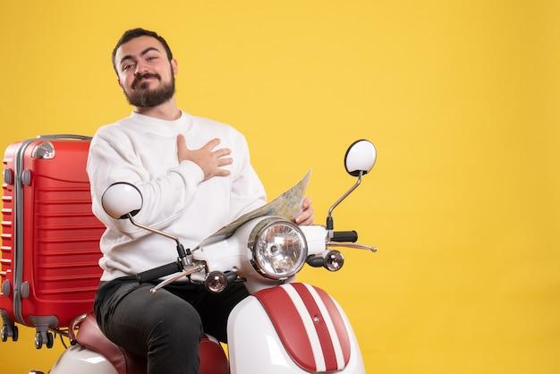 가방에 가방과 함께 오토바이에 앉아 웃는 남자와 여행 개념은 노란색에지도를 가리 킵니다