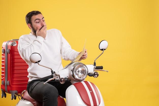 スーツケースを持ってバイクに座っている驚いた男が黄色の地図を見ている旅行のコンセプト