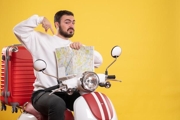 黄色の地図を指しているスーツケースを持ってオートバイに座っている驚いた男との旅行のコンセプト