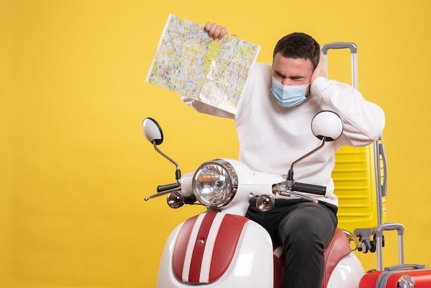 그것에 노란색 가방과 함께 오토바이에 앉아 노란색에지도를 보여주는 의료 마스크에 문제가있는 사람과 여행 개념