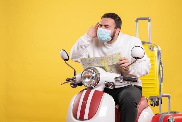 黄色いスーツケースを乗せたバイクに座り、頭痛に苦しんでいる地図を持った医療マスクを着た若い男との旅行のコンセプト