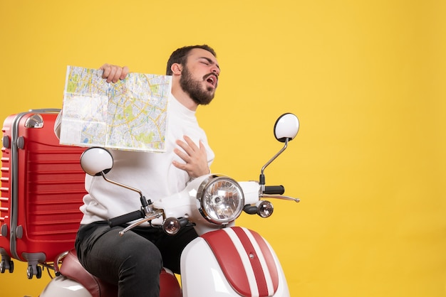 Concetto di viaggio con un giovane ragazzo seduto in moto con la valigia che soffre di infarto su di essa su giallo