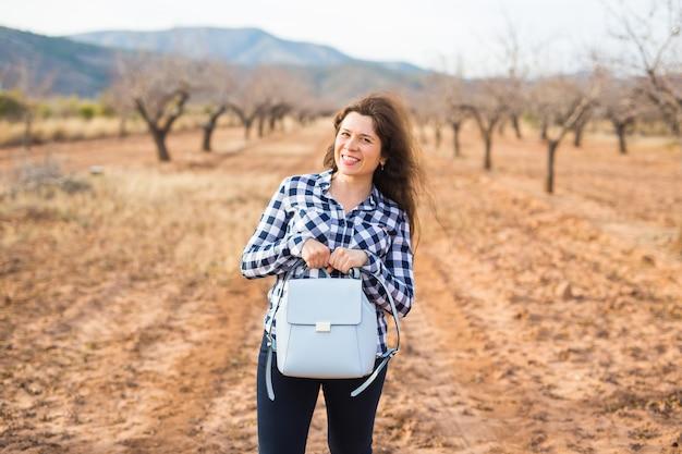 여행, 패션 및 사람들 개념입니다. 작은 가방을 들고 걷고 자연 위에 웃고 있는 행복한 젊은 여성.