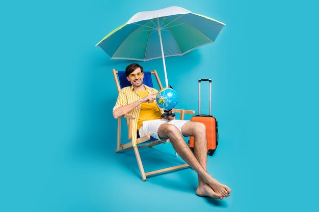 Next trip here. full body photo man relax rest sit chaise-lounge point finger globe have baggage luggage sunbath umbrella wear striped shirt yellow short isolated blue color background